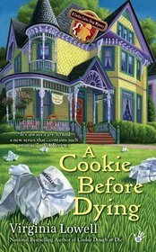 A Cookie Before Dying by Virginia Lowell Book Cover - Yellow and purple Victorian house in the background, crumpled pieces of paper on grass in foreground