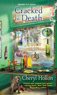 Cracked to Death by Cheryl Hollon book cover - Standing inside Webb's Glass Shop looking out the front window - glass creations hanging from window and on display table, dog under the table