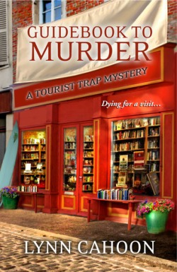 Guidebook to Murder by Lynn Cahoon book cover - Picture of the front of a bookstore, viewing the bookshelves inside and tables of display books outside