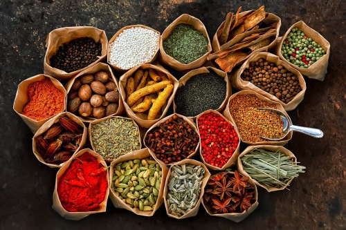 Photograph of bags of spices - Author unsure what they all are - peppercorns, chili powder, and star anise for certain