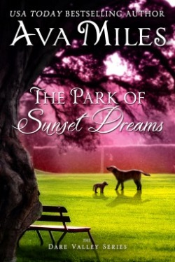 The Park of Sunset Dreams by Ava Miles - Picture of a park from the vantage point of standing under a tree - park bench under tree and two dogs on grassy area