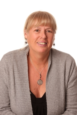 Photo of Vicky Delany, a middle-aged caucasian woman with blond hair pulled back and bangs, wearing a black camisole & grey cardigan