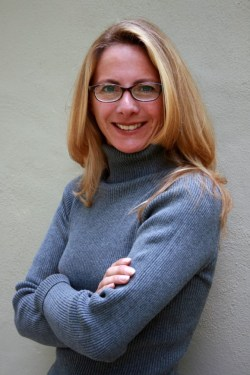 Middle-aged woman with slightly longer than shoulder length blond hair, with glasses - wearing a blue turtleneck sweater