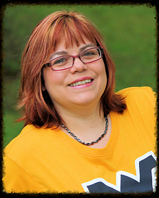 Christina Freeburn photo - middle-aged woman with reddish hair and glasses, wearing a gold West Virginia University shirt