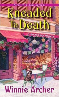 Kneaded to Death: A Bread Shop Mystery by Winnie Archer book cover - Features the front of the bread shop, Yeast of Eden, which has a display window full of various types of bread, a cafe table with chairs on the front sidewalk, and a pug sitting on one of the chairs