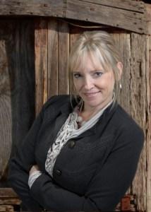 Winnie Archer, author, aka Melissa Bourbon-Ramirez - Middle-aged white woman with blond hair done in an up-twist, no glasses, wearing a grey shirt and dark grey blazer