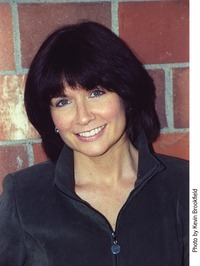 Middle aged caucasian woman with medium length black hair, no glasses, and wearing a black shirt