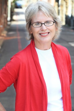 Barbara O'Connor, Author - Older white woman with short grey hair and glasses wearing a white shirt with a red cardigan