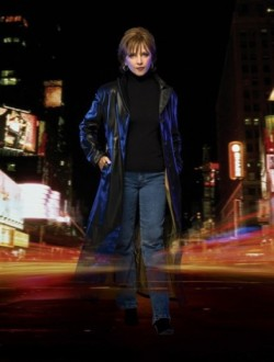 J.D. Robb, author - Middle aged woman with short brown hair, reverse teardrop shaped face, standing on a busy New York City street wearing jeans, a black shirt and a long black leather coat