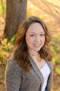 Author photo: Fall wooded background, young white woman with oval-shaped face, shoulder-length brown hair, no glasses, wearing a white top with a brown/tan cardigan and a gold necklace