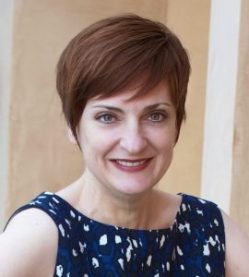 Author, Marla Cooper - Middle-aged white woman with reddish brown short hair, oval shaped face, no glasses, wearing a sleeveless navy blouse with white dots