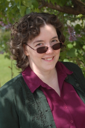 Morgan Talbot, author - White woman in her 30s or 40s, dark brown hair, wearing sunglasses halfway down her nose, a grey overshirt and a purple blouse