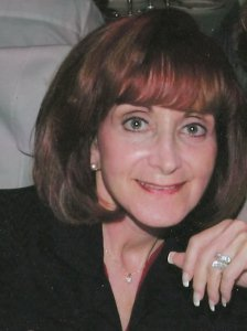 Author Sharon Pape - Older caucasian woman with auburn hair, wide eyes with no glasses, and a smile wearing a dark grey or black jacket.