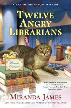 Book Cover: A Cat in the Stacks Mystery: Twelve Angry Librarians by Miranda James - auditorium background, Maine coon cat sitting on counter with a pile of books and a sign saying