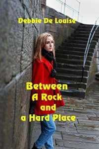 Book Cover: Between a Rock & a Hard Place by Debbie De Louise - white woman with long blond hair and a red pea coat standing against a cement block wall with a cement staircase behind her.