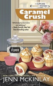 "Book Cover: A Cupcake Bakery Mystery - Caramel Crush by Jenn McKinlay - Marble countertop with a red platter with caramel cupcakes on it with ""Love"" in a circle and crossed out - canister of flour and window in background, rolling pin in foreground"