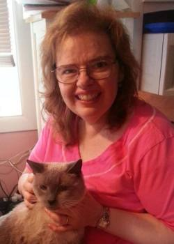 Author, Debbie De Louise - middle-aged white woman with glasses, shoulder-length brown hair and a big smile. She's holding a cat on her lap and wearing a pink t-shirt.