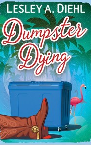 Book Cover: Lesley A. Diehl - Dumpster Dying: Tropical green and blue background with a blue dumpster, a pink flamingo behind the dumpster and a brown cowboy boot with blood on it in front of the dumpster