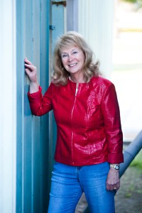 Lesley Diehl, Author - Middle-aged white woman with greying blond hair that hangs to her shoulders. She doesn't wear glasses. She's standing next to a blue paneled building in means and a red, shiny jacket