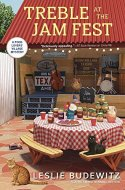 Book Cover: Treble at the Jam Fest - A Food Lovers' Village Mystery by Leslie Budewitz - background has a country music stage with guitars, double bass, and drum set - Foreground has a table with jam for sale, a pitcher of lemonade and two cats sitting on the ground