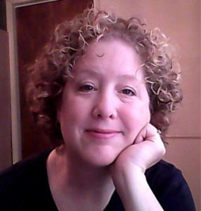 Author Teresa Trent - middle-aged white woman with curly ash brown hair, no glasses, leaning her chin on her hand wearing a black v-neck shirt