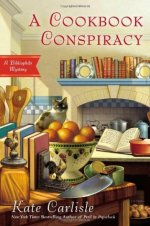Book Cover: A Cookbook Conspiracy: A Bibliophile Mystery: Kate Carlisle - kitchen setting - stove is set in a recessed area that looks like a fireplace. Pots on the stove - an open cookbook on a counter in the background with a pot w/ a lid next to it - Black & white cat sitting behind a colander full of oranges - butcher block table in foreground with knife, kitchen utensils, and cookbooks