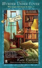 "Book Cover: Murder Under Cover - ""What dangers lurk between the sheets...?"" - A Bibliophile Mystery by Kate Carlisle - In the background there's a grey tabby cat looking out a window in between a comfy chair and an end table with flowers on it - there's a floor to ceiling bookshelf next to the end table. In the foreground is a bed with a gun lying on top and a scarf lying next to the gun"