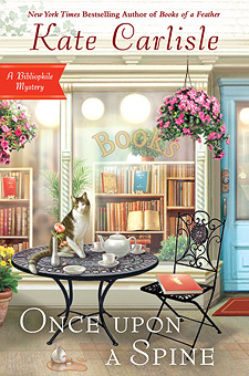 "Book Cover: Once Upon a Spine: A Bibliophile Mystery by Kate Carlisle - background is the front window of a bookshop - in the foreground are a wrought iron table and chair with a teapot & cups/saucers on the table along with a cat. On the chair is a copy of ""Alice in Wonderland"""