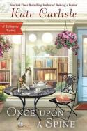 Book Cover: Once Upon a Spine: A Bibliophile Mystery by Kate Carlisle - Background shows a bookstore front window - foreground has tea service sitting on a wrought iron table with a cat on the table and a copy of Alice in Wonderland on a wrought iron chair