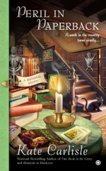 "Book Cover: Peril in Paperback - A Bibliophile Mystery by Kate Carlisle - ""A week in the country turns deadly..."" - the background has a staircase with a black cat sitting on the bottom and a suit of armor and a pinball machine sitting next to the staircase. The foreground has a green table with noir paperbacks, other piled books, and a lit candle."