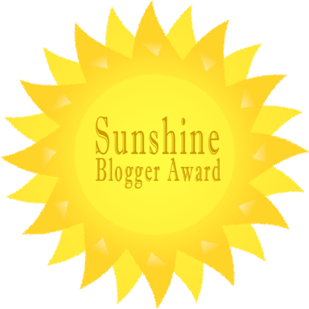 "Large gold and yellow sun with the words ""Sunshine Blogger Award"" written in the center of the sun."