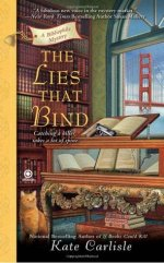 "Book Cover: The Lies that Bind - A Bibliophile Mystery by Kate Carlisle - ""Catching a killer takes a lot of spine."" - Background includes a window overlooking the Golden Gate bridge and a floor to ceiling bookshelf. The foreground contains a display case full of books with a book displayed on top and a gun sitting on top of the book on top of the display case. There's an orange tabby cat sitting on the floor next to the case."