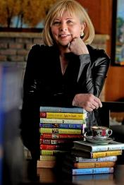Author Photo: Gerry Schmitt - middle-aged white woman with blond hair and no glasses - wearing a black shirt and leaning against a stack of her books