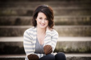Author Jenny B. Jones - Young white woman with dark brown hair stopping just above her shoulders sitting on cement steps wearing a grey and white striped cardigan, grey shell, and pants