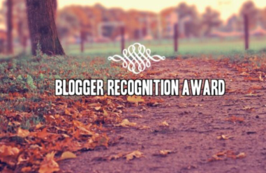 "Background: A Fall pathway lined with fallen leaves - text is centered and in white ""Blogger Recognition Award"" with a curly, fancy little white graphic above it"
